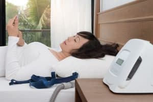 Woman in bed not using CPAP machine