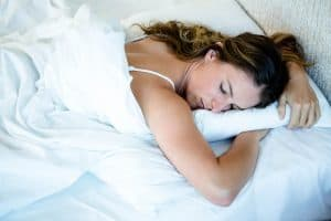 Woman sleeping comfortably on stomach in bed