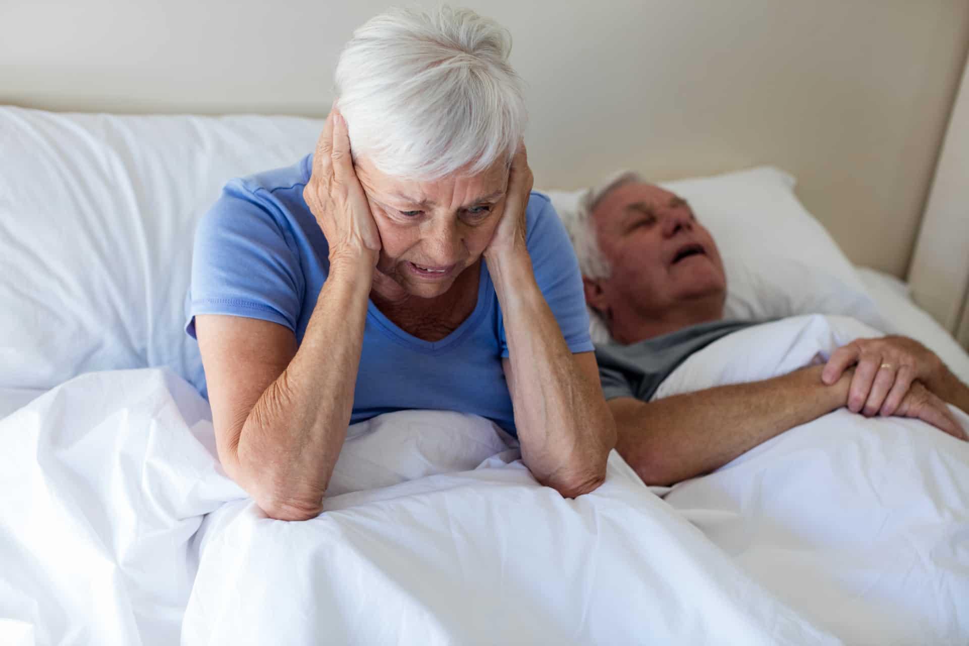 Senior woman disturbed by man snoring